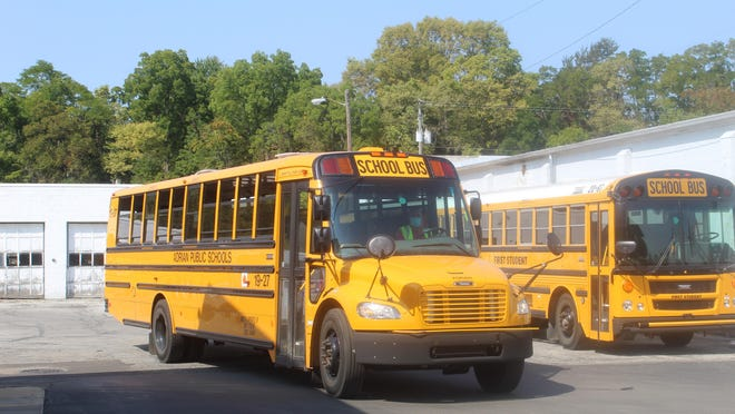 An Adrian Public Schools bus leaves the lot on Race Street to take students home Thursday afternoon.