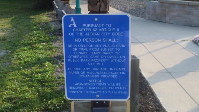 A sign notifying trail-goers of a city of Adrian ordinance change is pictured at the Kiwanis Trail just south of Maumee Street. The Adrian City Commission voted to prohibit camping and change park hours on Monday. The signs will be posted in all parks.