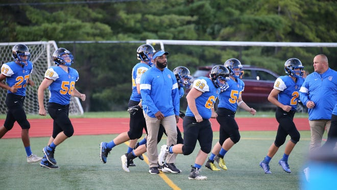 Madison football coach Taz Wallace, foreground, leads his team onto the field before a game against Sand Creek last September at Siena Heights University.