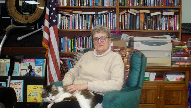 Barb Sell, librarian of Read It and Reap Library in Sand Creek, sits with one of the her library cats, Hairy. Sell lost 40,000-some books in a fire last month. The Sand Creek community has rallied around one of its own with an outpouring of support and donations.