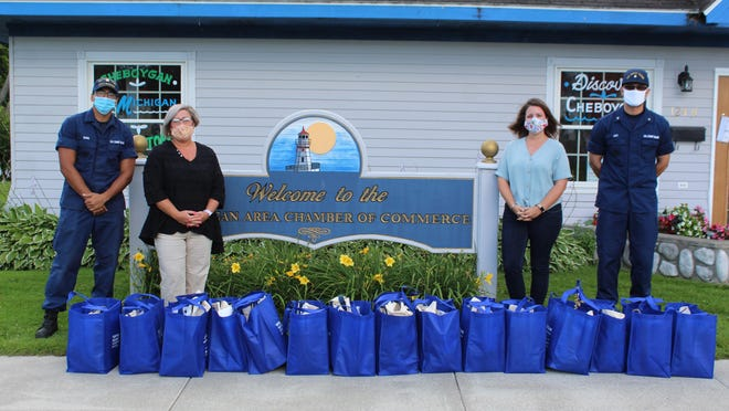 """Polly Schneider, the assistant director of the Cheboygan Area Chamber of Commerce, presented Erica Castro, the United States Coast Guard Ombudsman and two representatives from the United States Coast Guard, Kristian Lett and Carter Evans, with """"Welcome to Cheboygan"""" bags to be given to new transfers of the Coast Guard to Cheboygan. Photo by Kortny Hahn"""
