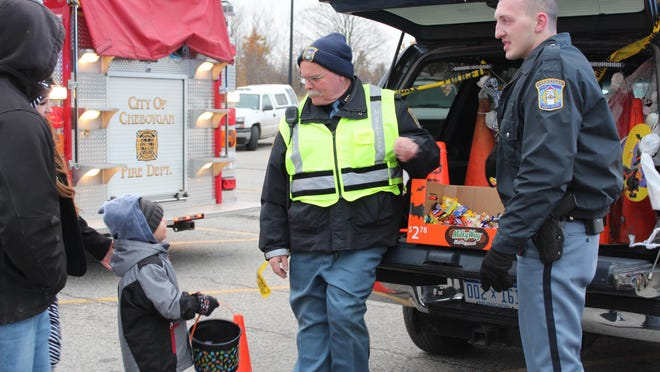 Cheboygan Department of Public Safety Director Kurt Jones and Officer Bret Auger were among the many people who handed out candy to the children at the Trunk or Treat in Walmart parking lot last year. However, with corporate restrictions, there will be no trunk or treat this year. Tribune File Photo by Kortny Hahn
