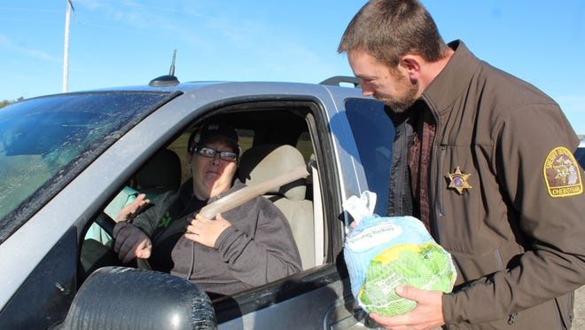 Last year, Cheboygan County Sheriff's Deputy Matt LaCross was among the deputies who were pulling people over and giving them a turkey to help them celebrate Thanksgiving. LaCross was so happy when he was able to talk to the drivers and find out how much good it was doing to give out the birds to help with dinner. Tribune File Photo by Kortny Hahn