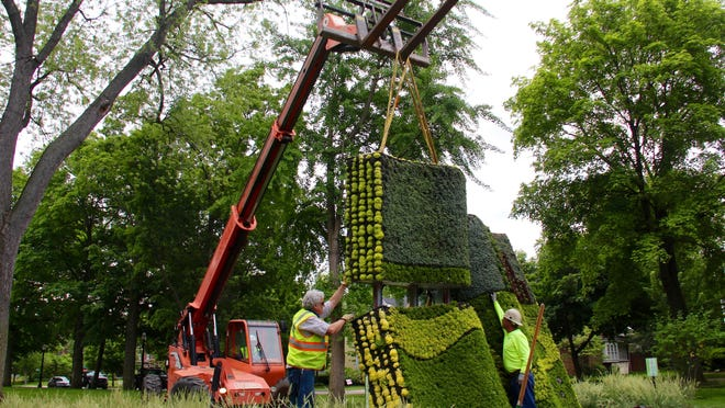 "A crew installs the floral ""living"" sculpture of ""The Wonderful Wizard of Oz"" book by L. Frank Baum in Centennial Park on Friday, June 12, 2020."