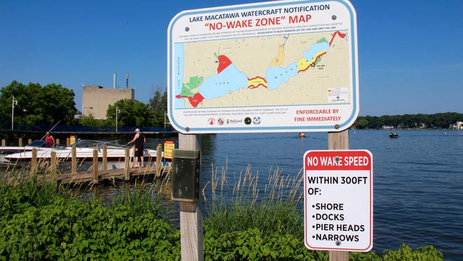 """New temporary no-wake regulations are now in effect on Lake Macatawa, including no-wake zones within 300 feet of the shore, docks and piers and no-wake for the part of Lake Macatawa known as """"the narrows,"""" as this sign at the Kollen Park boat launch in Holland indicates."""