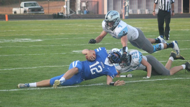 Ionia senior quarterback Blake Bookie (No. 12) is tackled by Lansing Catholic defenders during a varsity football game Friday, Sept. 25, at Lloyd T. Smith Memorial Field in Ionia. Lansing Catholic won 42-3.