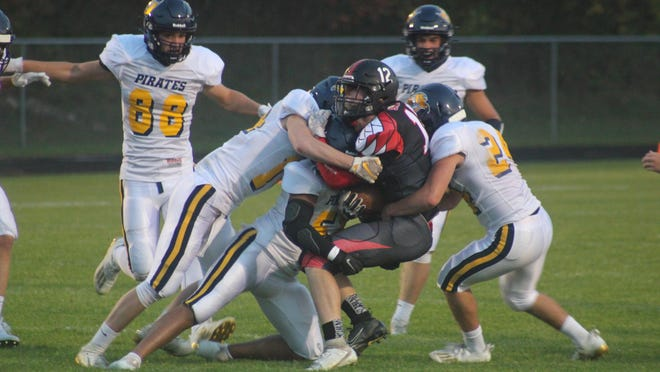 The Pewamo-Westphalia defense brings down senior Ty Wood (No. 12) of Saranac during a varsity football game Friday, Oct. 9, at Saranac Jr./Sr. High School. P-W won 63-0.