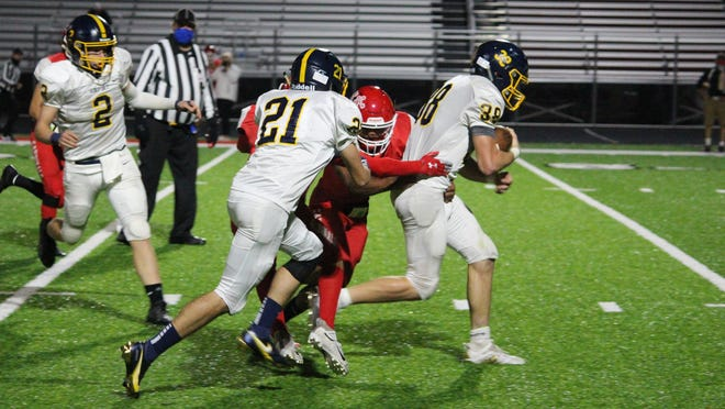 Airport's Jacob Pac powers for yards during a 46-7 win over Melvindale Friday night. The Airport blockers pictured are Nikolas Hammond (2) and Trent Books (21).