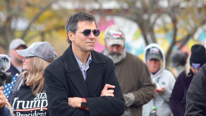 """Ryan Kelley, an Allendale Township planning commissioner, stands during a """"freedom rally"""" in Allendale, Mich., Saturday, Oct. 24, 2020. Allendale residents have called for Kelley's removal again, following the surfacing of images of Kelley among the mob during the protest-turned-riot in the Capitol on Jan. 6."""