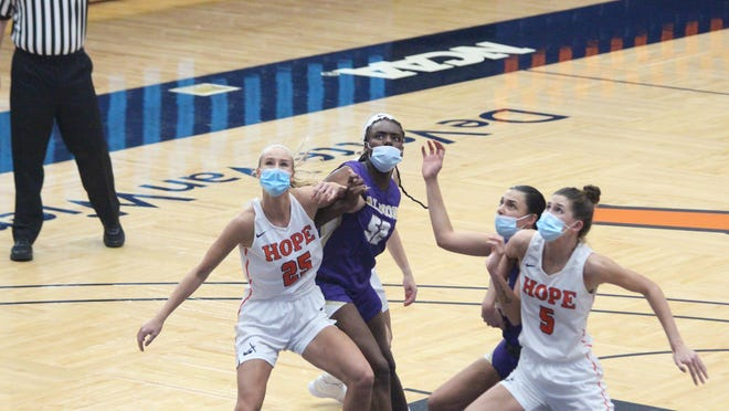 Hope's Olivia Voskuil (right) and Ashleigh Thomas (left) box out for a rebound in the team's win over Albion on Saturday, Jan 23, 2021 in Holland.