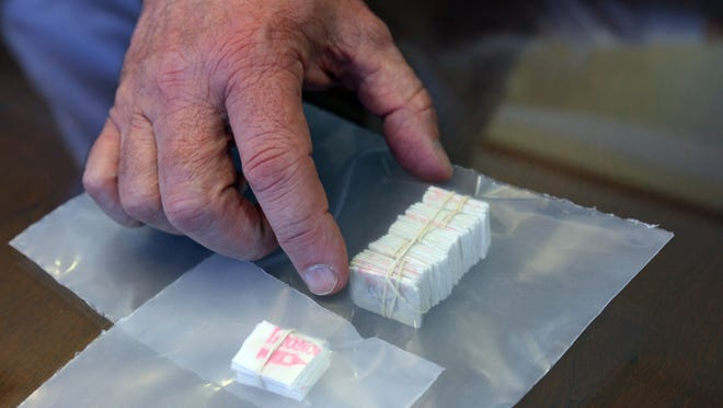 Ocean County Prosecutor Joseph D. Coronato displays an example of a stamped bundle and brick of heroin at the Ocean County Prosecutor's Office in April 2013. A vehicle stop led to the arrest of a Keansburg man on narcotics charges after he was found to be in possession of xanax, marijuana and heroin, police said Wednesday.
