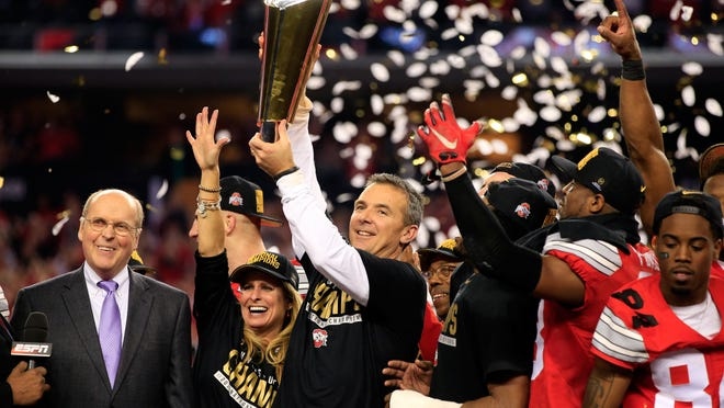 Ohio state head football coach Urban Meyer hoist the trophy after defeating the Oregon Ducks 42 to 20 in the College Football Playoff National Championship Game on Monday at AT&T Stadium in Arlington, Texas.