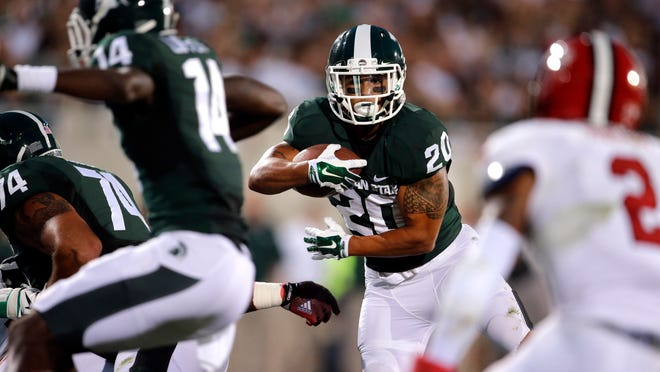 Michigan State running back Nick Hill (20) looks for running room on a 17-yard touchdown run against Jacksonville State. When No. 7 Michigan State plays at No. 3 Oregon on Saturday, the team with the old-school offense will be the unusual one.