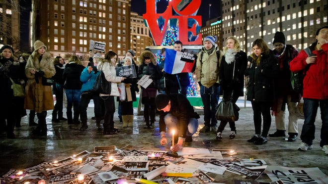 People gather to pay tribute to victims of the terrorist attack against the French satirical weekly Charlie Hebdo on Jan. 9, at JFK Plaza, commonly known as Love Park, in Philadelphia. On Jan. 7, masked gunmen stormed the Paris offices of the weekly newspaper that caricatured the Prophet Muhammad, killing at least 12 people.