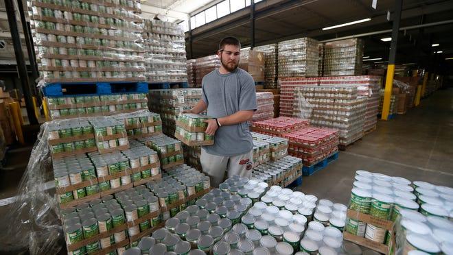 Dalton Taylor stacks green beans at the Freestore Foodbank. School vacations mean supplies may get tight.