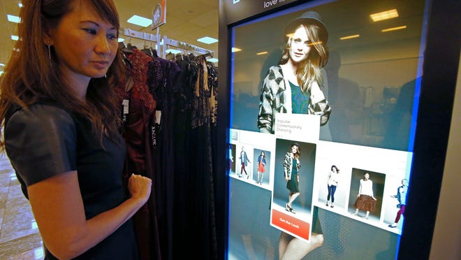 """Orlena Shea, manager of the Macy's at Kenwood Towne Centre, demonstrates the """"look book,"""" which assists shoppers searching for that certain fashion look . The retailer has installed several   look books and   point-of-purchase   screens at the Kenwood store."""