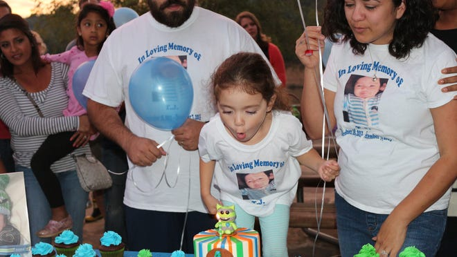 "Aurora Castellon, 4, blows out a candle in behalf of her brother, Thomas, ""T.J."" Castellon, who would've been one on Thursday, but died when he was 7-months-old from Shaken Baby Syndrome at the hands of a close family friend. Thomas and Lucy Castellon, his parents look on."