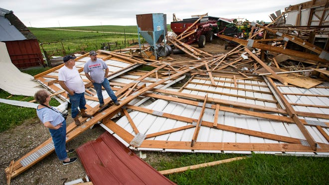 Ardith Buckner, Arnold Lewis, center, and son Scott take inventory of the damage to Lewis' home and farm after storms and high winds raked the area near Stuart on Monday.