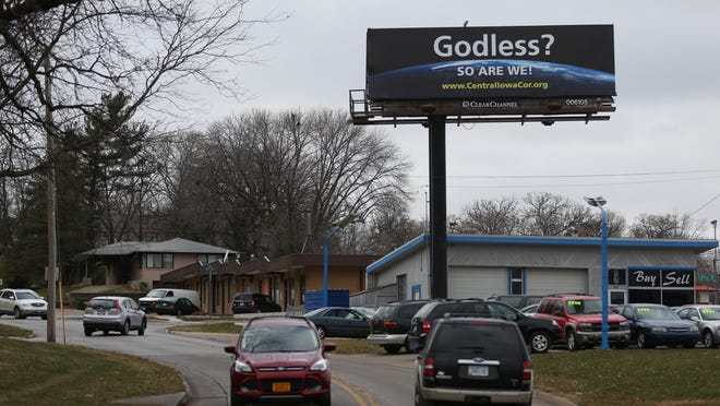 """A billboard is seen above Douglas avenue on Thursday, Nov. 12, 2014, in Des Moines, Iowa. """"Godless, so are we!"""" These words, superimposed over an image of the earth from space, are appearing on four prominent billboards across the state of Iowa and into Illinois. This marks the formal launch of the Central Iowa Coalition of Reason and the Eastern Iowa Coalition of Reason."""