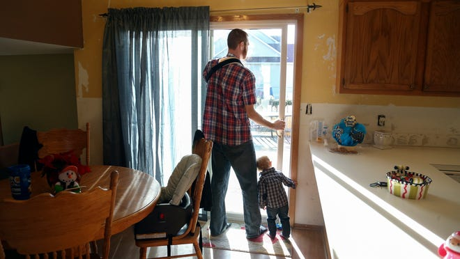 Zach Whitehill looks out the sliding glass door with his son, Gage, inside their home on Wednesday in Pleasant Hill. Whitehill was a victim in a random shooting spree in Pleasant Hill last month.