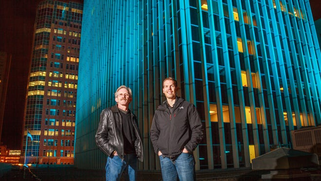 Mike Lambert and Kris Kunze from KCL Engineering stand outside the Financial Center Building in downtown Des Moines. The company provided the lighting elements for the building.