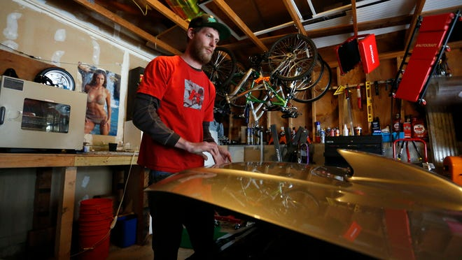 In this Jan. 13, 2015 photo, Ian Sullivan closes the hood of his custom racing Subaru, at home in Evergreen, Colo. Sullivan's has struggled daily to cope emotionally ever since 2012, when a heavily armed gunman opened fire in a movie theater where his six year old daughter Veronica and Sullivan's x-wife were watching a movie, leaving 12 dead, including his daughter Veronica.