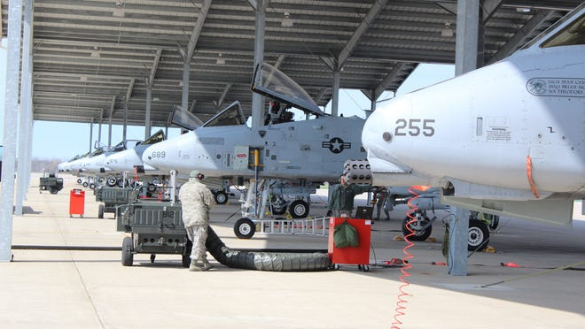 A row of A-10 fighter jets sit under a canopy at the Selfridge Air National Guard Base, Tuesday, March 27, 2012.