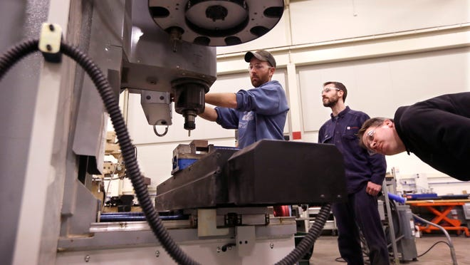 Brad Bancroft, left, Nate Joseph and Adam Woodhams at a precision machining class at Lansing college. Gov. Rick Snyder covets such skills.