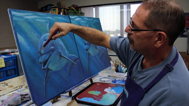 Frank DiMaria, a volunteer with the disABLEd Artists program, paints a ceiling tile and matching canvas.