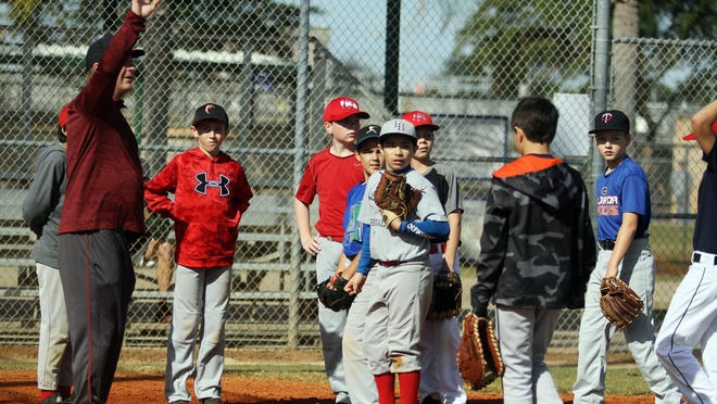 Scot Welch, head coach of the Major Red Sox 9-12yr, one of the squads in the Fort Myers American Little League baseball team, calls his team to home plate during fielding drills Saturday morning at Fleishman Sports Complex in Fort Myers.