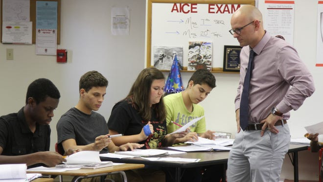 North Fort Myers High School's Adam Molloy, a Golden Apple winner, makes himself available to a student who needed help while working on a project in class recently.