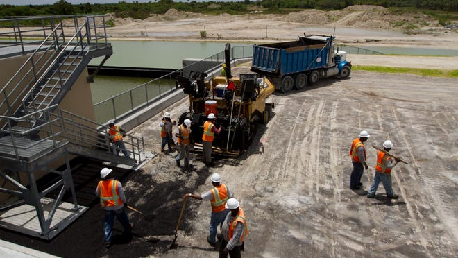 Paving crews work on the Merrit Pump station in the Picayune strand on Friday. The pump station is one of three that is being built as part of the Everglades restoration project.