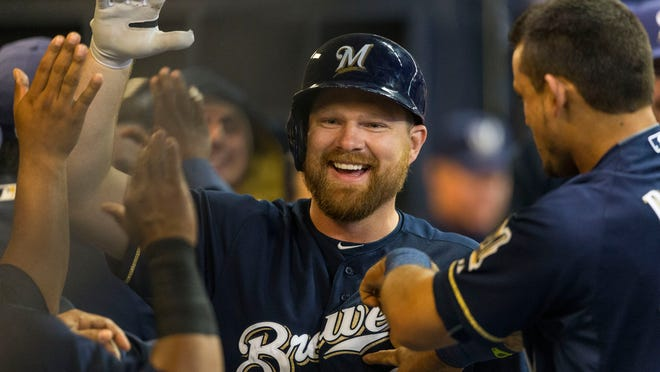 Milwaukee Brewers first baseman Adam Lind is congratulated by teammates after hitting a two-run homer off Colorado Rockies pitcher Eddie Butler during the third inning of Wednesday's game.