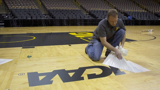 Facilities Service Coordinator Mike Patterson prepares Carver-Hawkeye Arena on March 18, 2015, for the women's NCAA Tournament by affixing a logo to the court.