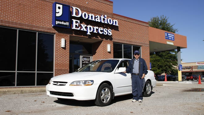 Raymond Moore, a Goodwill Donations Express attendant who works in Jackson and Lexington, stands beside the car he received Friday through Goodwill's Wheels-to-Work program, which helps Goodwill employees and clients who need reliable transportation to get to work.