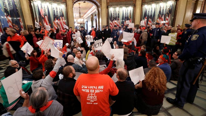 Protesters sit in the rotunda of the State Capitol in 2012  in an unsuccessful effort to block passage of right-to-work legislation. The writer suggests such laws cause more people to hold two jobs.