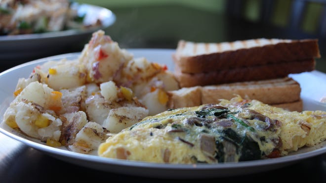 The 'Healthy & Delicious' omelette, prepared with mushrooms, spinach, tomatoes and onions, is served with home fries and toast at Healthy & Delicious restaurant in Morris Plains.