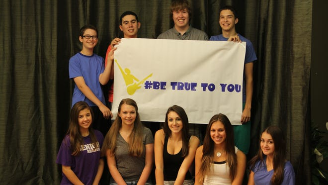 Students hold a banner for Be True to You, a school assembly program created by Ashley Tobias.