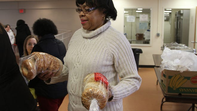 Manager Gloria Leak fills up the bread basket at the food pantry inside Fellowship Hall of Bethel A.M.E. Church in Morristown.