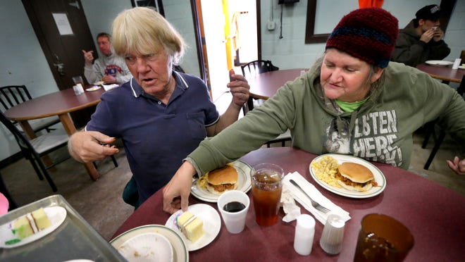 Karl Danny Howe, left and Delores McMullen pick out a piece of cake to complete their hot lunch at the Community Cafe at The Journey Home Nov. 18.