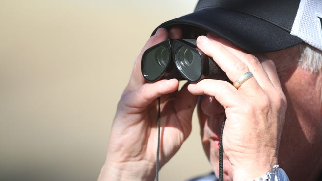 A fan peers through binoculars to catch the action up close during the 2014 Humana Challenge.
