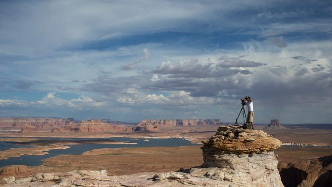 The 50-year-old Lake Powell, whose vista Mylo Fowler photographs at Alstrom Point, Utah, is less than half-full because of a years-long drought. photos by mark Henle/The Republic lake powell   08/019/2013   Mylo Fowler (CQ) photographs Lake Powell from Alstrom Point, Utah.   Mark Henle/The Arizona Republic