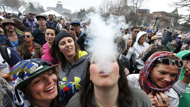 With the Colorado state capitol building visible in the background, party-goers dance and smoke pot at the 4/20 marijuana festival in Denver.