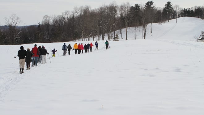 Participants are shown taking a snowshoe walk at Olana State Historic Site.