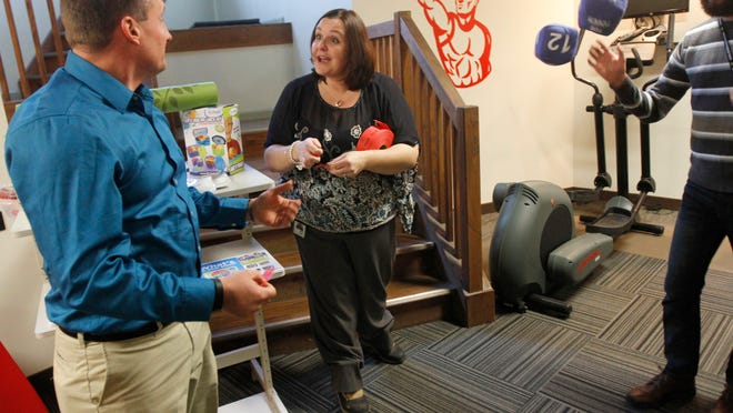 Kara Martin, director of Mission, Vision & Character Advancement at D4, jokes with Keith Ogles, Systems Administrator, after giving him raffle tickets at the re-launching of D4's wellness center Monday. Martin is in charge of wellness programs and more at D4.