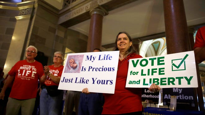 Joanne Schrader holds signs as she gathers with other abortion opponents in the rotunda of the Missouri Capitol Wednesday, Sept. 10, 2014, in Jefferson City, Mo.
