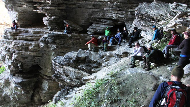 Hikers take a break after climbing a steep slope beneath the stone cathedral — a collapsed cave on the way to the Eye of the Needle.