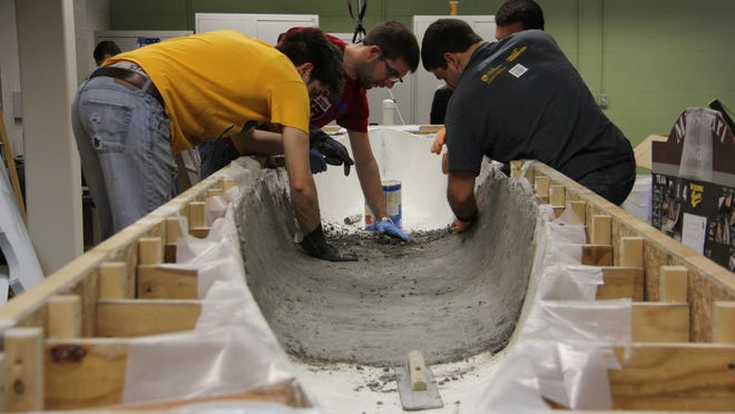 MSU Concrete Canoe Team members pound wet concrete onto the form of their 19-foot canoe.
