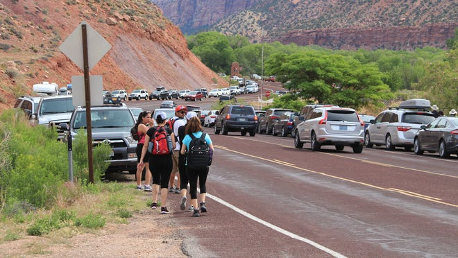 Cars stretch into neighboring Springdale and beyond outside of Zion National Park.