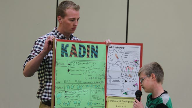 Kadin Adsit, right, talks about his enrichment work over the past 10 weeks during a student showcase at Bannach Elementary School as his mentor, Rudy Botz, a student at the University of Wisconsin-Stevens Point, holds his poster.